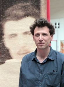 French bookseller Alban Causse poses in front of a blown-up print of a previously unseen photo of French poet Rimbaud at the Paris Old Books fair in the Grand Palais. Causse and his colleague Jacques Desse found the photo at a flea market.